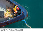 Man at work on a bow of a tug (2015 год). Редакционное фото, фотограф EugeneSergeev / Фотобанк Лори
