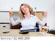 Blonde Frau am Schreibtisch streckt ihre Muskeln. Стоковое фото, фотограф Zoonar.com/Robert Kneschke / age Fotostock / Фотобанк Лори