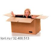 Kind in Umzugskarton. Liegt beim Umzug in Schachtel. Стоковое фото, фотограф Zoonar.com/Erwin Wodicka / age Fotostock / Фотобанк Лори