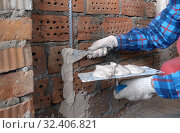 Купить «Person in work gloves ( hand in the frame) holds a trowel with plaster and attaches construction beacons to a brick wall with a spatula», фото № 32406821, снято 11 декабря 2019 г. (c) Куликов Константин / Фотобанк Лори
