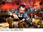 Купить «Male worker working on leather for belt in leather», фото № 32406853, снято 12 июля 2020 г. (c) Яков Филимонов / Фотобанк Лори
