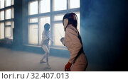 Купить «Two young women fencers having a training duel in the smoky studio», видеоролик № 32407013, снято 1 апреля 2020 г. (c) Константин Шишкин / Фотобанк Лори