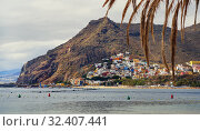 Waterside distant view to Playa de Las Teresitas beach picturesque famous place for tourists, hillside town houses mountainous terrain and calm Atlantic Ocean. Tenerife, Canary Islands, Spain (2019 год). Стоковое фото, фотограф Alexander Tihonovs / Фотобанк Лори