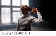 Купить «A young woman fencer she lets her hair down from the bun», видеоролик № 32407461, снято 10 апреля 2020 г. (c) Константин Шишкин / Фотобанк Лори