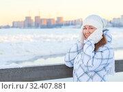 Купить «Frozen and smiling woman covering her ears with hands in woolen mittens, standing outdoor at cold weather in winter season», фото № 32407881, снято 19 января 2014 г. (c) Кекяляйнен Андрей / Фотобанк Лори