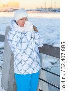 Купить «Frozen woman standing on urban bridge, warming her hands dressed in woolen mittens, winter season», фото № 32407885, снято 19 января 2014 г. (c) Кекяляйнен Андрей / Фотобанк Лори