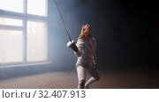 Купить «A young woman fencer with loose hair in white protective costume performing basic attack movements», видеоролик № 32407913, снято 1 апреля 2020 г. (c) Константин Шишкин / Фотобанк Лори