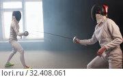 Купить «Two young women having an intense training in a fencing duel in the dark smoky studio», видеоролик № 32408061, снято 10 апреля 2020 г. (c) Константин Шишкин / Фотобанк Лори