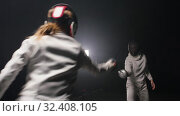 Купить «Two young women having training in a fencing duel in the smoky studio - greeting each other and starting the duel», видеоролик № 32408105, снято 1 апреля 2020 г. (c) Константин Шишкин / Фотобанк Лори
