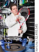 Купить «Man is looking on tennis racket in time repairs it indoors», фото № 32410545, снято 7 февраля 2018 г. (c) Яков Филимонов / Фотобанк Лори