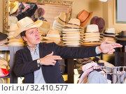 Купить «happy adult male try on cowboy hat at the shopping center», фото № 32410577, снято 2 мая 2017 г. (c) Яков Филимонов / Фотобанк Лори