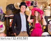 Купить «attractive female and man choosing hats in the store», фото № 32410581, снято 2 мая 2017 г. (c) Яков Филимонов / Фотобанк Лори