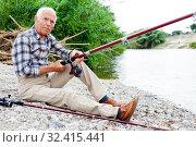 Купить «Aged man fishing at lakeside», фото № 32415441, снято 10 июня 2018 г. (c) Яков Филимонов / Фотобанк Лори