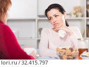 Unhappy female talking with mother at table. Стоковое фото, фотограф Яков Филимонов / Фотобанк Лори