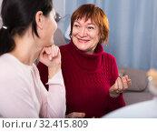 Купить «Smiling woman talking with daughter at sofa», фото № 32415809, снято 23 ноября 2017 г. (c) Яков Филимонов / Фотобанк Лори