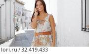 Купить «Stylish pretty brunette in light summer dress using smarpthone for conversation while posing at sunny street and smiling away.», фото № 32419433, снято 30 мая 2020 г. (c) easy Fotostock / Фотобанк Лори