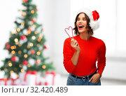 Купить «happy young woman in santa hat on christmas», фото № 32420489, снято 30 сентября 2019 г. (c) Syda Productions / Фотобанк Лори