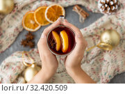 Купить «hands with glass of hot mulled wine on christmas», фото № 32420509, снято 4 октября 2018 г. (c) Syda Productions / Фотобанк Лори