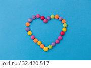 Купить «candy drops in shape of heart on blue background», фото № 32420517, снято 11 декабря 2018 г. (c) Syda Productions / Фотобанк Лори