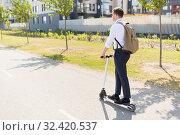 Купить «businessman with backpack riding electric scooter», фото № 32420537, снято 1 августа 2019 г. (c) Syda Productions / Фотобанк Лори