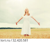 Купить «smiling young woman in white dress on cereal field», фото № 32420581, снято 31 июля 2016 г. (c) Syda Productions / Фотобанк Лори