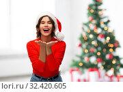 Купить «happy young woman in santa hat sending air kiss», фото № 32420605, снято 30 сентября 2019 г. (c) Syda Productions / Фотобанк Лори