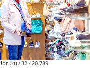 Russia, Samara, May 2016: showcase of a shoe store, a woman chooses shoes. Редакционное фото, фотограф Акиньшин Владимир / Фотобанк Лори