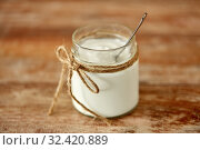 yogurt or sour cream in glass jar on wooden table. Стоковое фото, фотограф Syda Productions / Фотобанк Лори