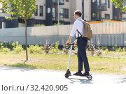 Купить «businessman with backpack riding electric scooter», фото № 32420905, снято 1 августа 2019 г. (c) Syda Productions / Фотобанк Лори