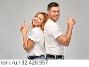 Купить «couple in white t-shirts shirts making gun gesture», фото № 32420957, снято 6 октября 2019 г. (c) Syda Productions / Фотобанк Лори