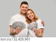 Купить «happy couple in white t-shirts with dollar money», фото № 32420961, снято 6 октября 2019 г. (c) Syda Productions / Фотобанк Лори