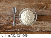 Купить «close up of cottage cheese in bowl on wooden table», фото № 32421069, снято 16 августа 2018 г. (c) Syda Productions / Фотобанк Лори