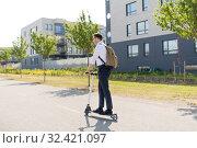 Купить «businessman with backpack riding electric scooter», фото № 32421097, снято 1 августа 2019 г. (c) Syda Productions / Фотобанк Лори