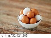 Купить «close up of eggs in ceramic bowl on wooden table», фото № 32421205, снято 16 августа 2018 г. (c) Syda Productions / Фотобанк Лори