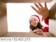 Купить «happy young woman looking into open christmas gift», фото № 32421213, снято 9 декабря 2018 г. (c) Syda Productions / Фотобанк Лори