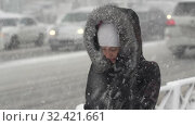 Купить «Young woman in black winter jacket walking sidewalk during Pacific snow cyclone», видеоролик № 32421661, снято 15 ноября 2019 г. (c) А. А. Пирагис / Фотобанк Лори