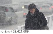 Купить «Woman in black jacket walking on sidewalk during snowfall, Pacific snow cyclone», видеоролик № 32421689, снято 15 ноября 2019 г. (c) А. А. Пирагис / Фотобанк Лори
