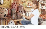 Купить «Young positive woman choosing ceramic products in pottery store», видеоролик № 32421945, снято 6 декабря 2019 г. (c) Яков Филимонов / Фотобанк Лори