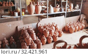 Купить «Handmade jugs from baked clay on shelf in pottery workshop», видеоролик № 32421961, снято 28 мая 2020 г. (c) Яков Филимонов / Фотобанк Лори