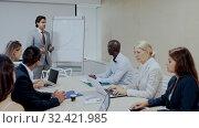 Купить «Businessman making presentation on staff meeting at office», видеоролик № 32421985, снято 16 ноября 2019 г. (c) Яков Филимонов / Фотобанк Лори