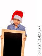 Kleiner Junge mit Nikolausmütze hält eine Tafel, Symbol für Weihnachten, Kindheit, Marketing. Стоковое фото, фотограф Zoonar.com/Erwin Wodicka / age Fotostock / Фотобанк Лори