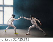 Купить «A fencing training in the studio - two women in protective costumes having a duel - poking with a swords in each other», фото № 32425813, снято 4 ноября 2019 г. (c) Константин Шишкин / Фотобанк Лори
