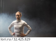 Купить «A young woman fencer standing in the dark smoky studio», фото № 32425829, снято 4 ноября 2019 г. (c) Константин Шишкин / Фотобанк Лори