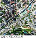 Купить «Aerial city view with crossroads and roads, houses, buildings, parks and parking lots. Sunny summer panoramic image», фото № 32426821, снято 21 января 2020 г. (c) Александр Маркин / Фотобанк Лори
