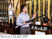 Man owner of hunting shop offering shotgun indoors. Стоковое фото, фотограф Яков Филимонов / Фотобанк Лори