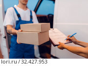 Купить «Deliveryman gives parcel to female recipient», фото № 32427953, снято 8 сентября 2019 г. (c) Tryapitsyn Sergiy / Фотобанк Лори