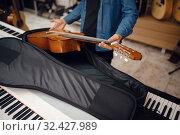 Купить «Guitarist puts guitar in the case, music store», фото № 32427989, снято 11 сентября 2019 г. (c) Tryapitsyn Sergiy / Фотобанк Лори