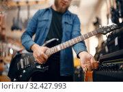Купить «Guitarist plays on electric guitar in music store», фото № 32427993, снято 11 сентября 2019 г. (c) Tryapitsyn Sergiy / Фотобанк Лори