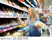 Portrait of woman holding assortment of cheese in grocery shop. Стоковое фото, фотограф Яков Филимонов / Фотобанк Лори