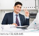 Купить «Smiling young man reading documents about the transaction», фото № 32428645, снято 18 мая 2017 г. (c) Яков Филимонов / Фотобанк Лори